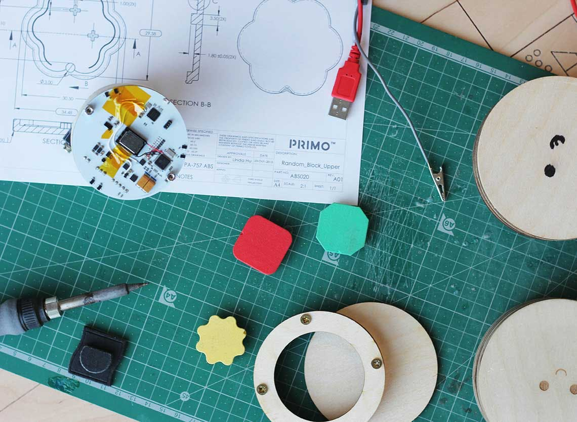 Mechanical pieces and simple plastic shapes lie on top of a cutting mat and blueprints for the product
